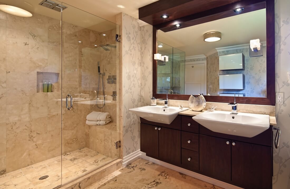 Luxurious bathroom remodeled with natural stone shower and cherry wood vanity