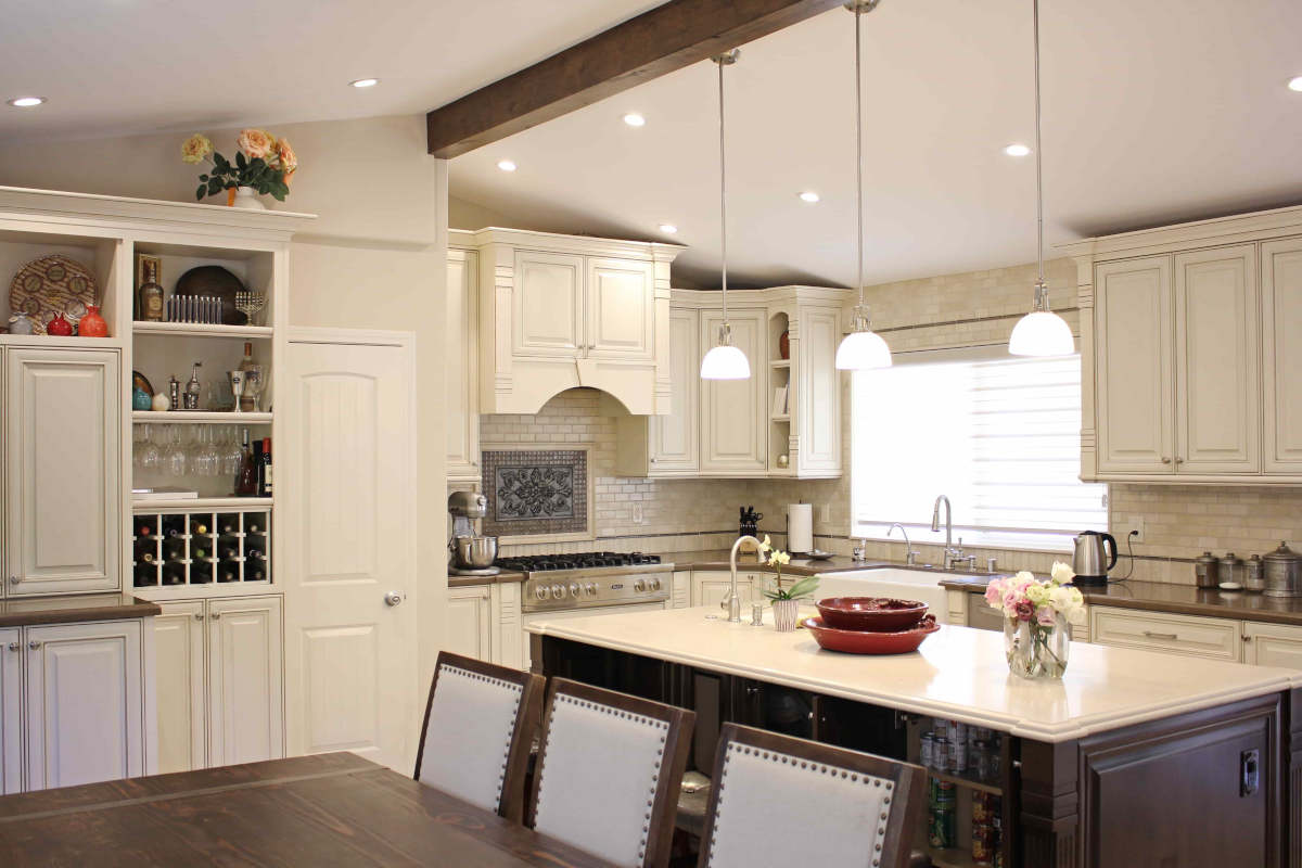 A newly remodeled kitchen in Sherman Oaks, CA by A-List Builders, with pendant lights hanging from an exposed beam over a center island, and white cabinetry.