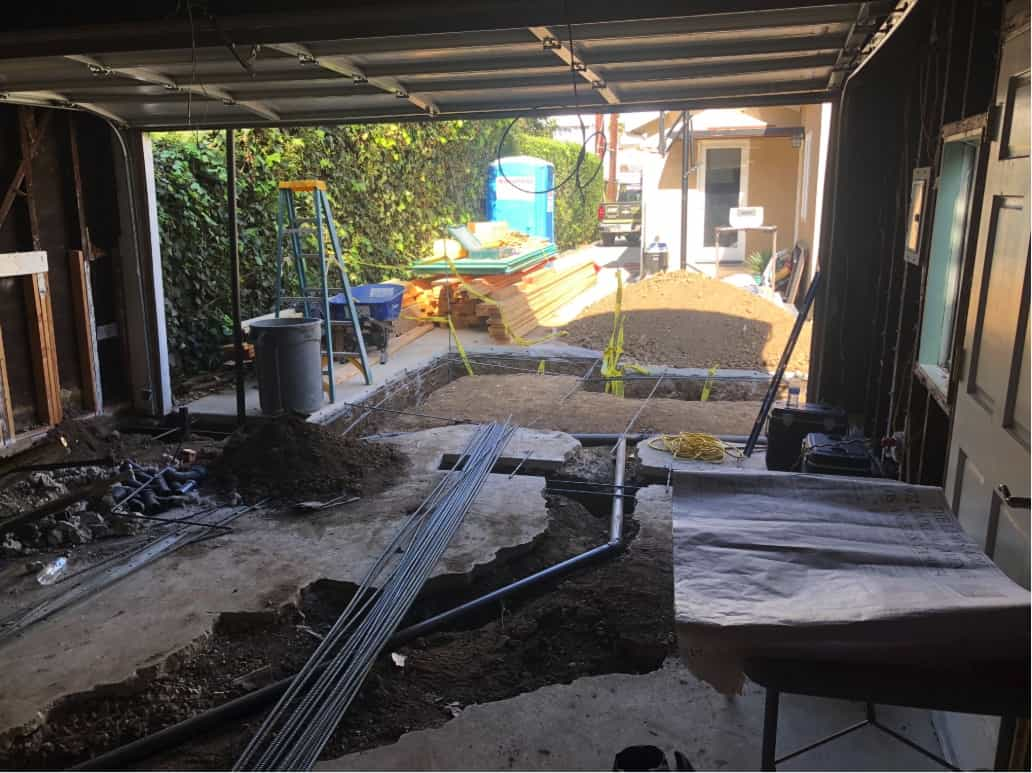 A garage and driveway are torn up to expose buried pipes, part of a home remodel in Beverlywood, CA by Los Angeles design-build firm A-List Builders.
